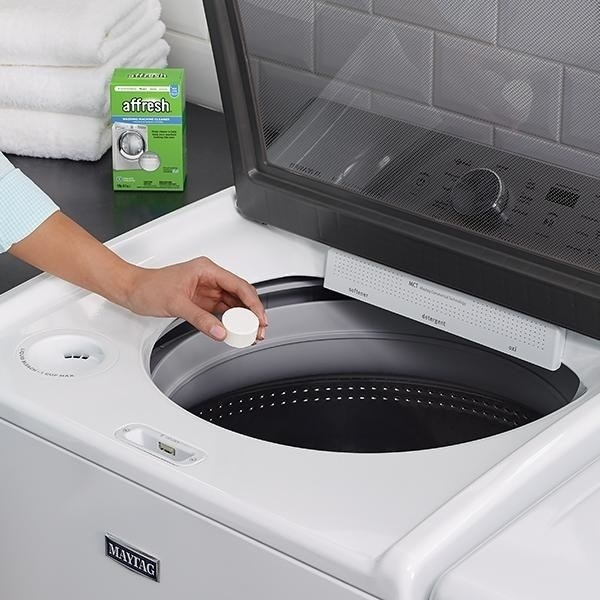 models hand dropping 1/4c-ish size tablet into washer