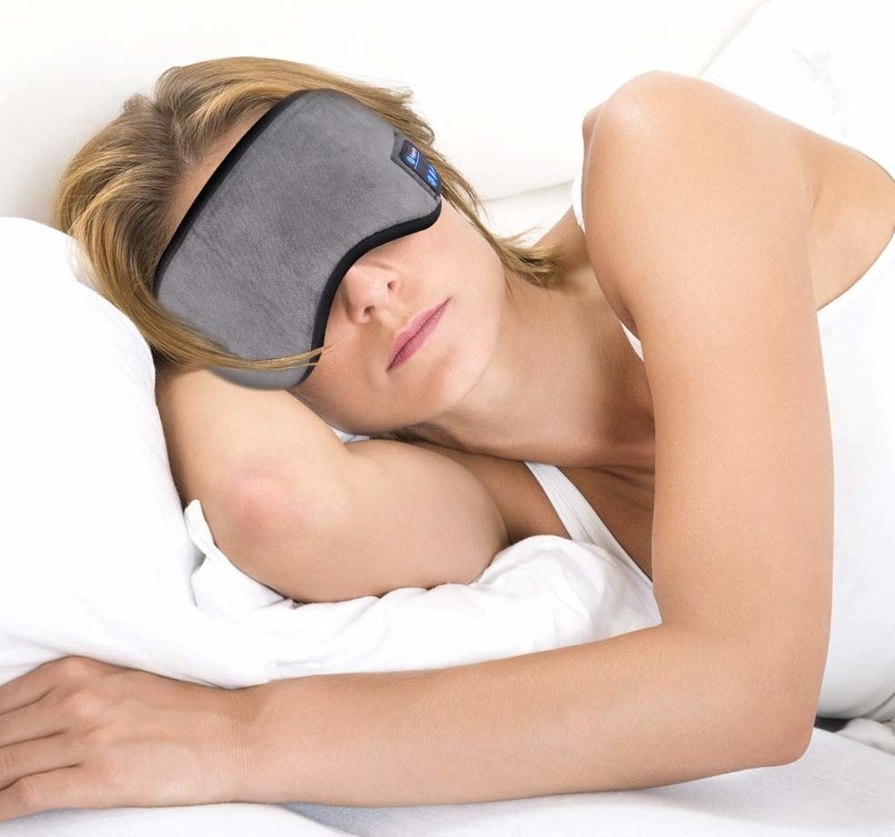 A woman lies on her side in bed with a sleep mask over her eyes.