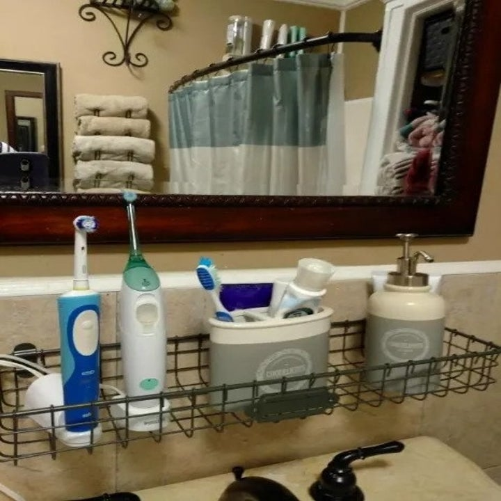a reviewer's photo of the baskets hanging in a bathroom with toothbrushes on it