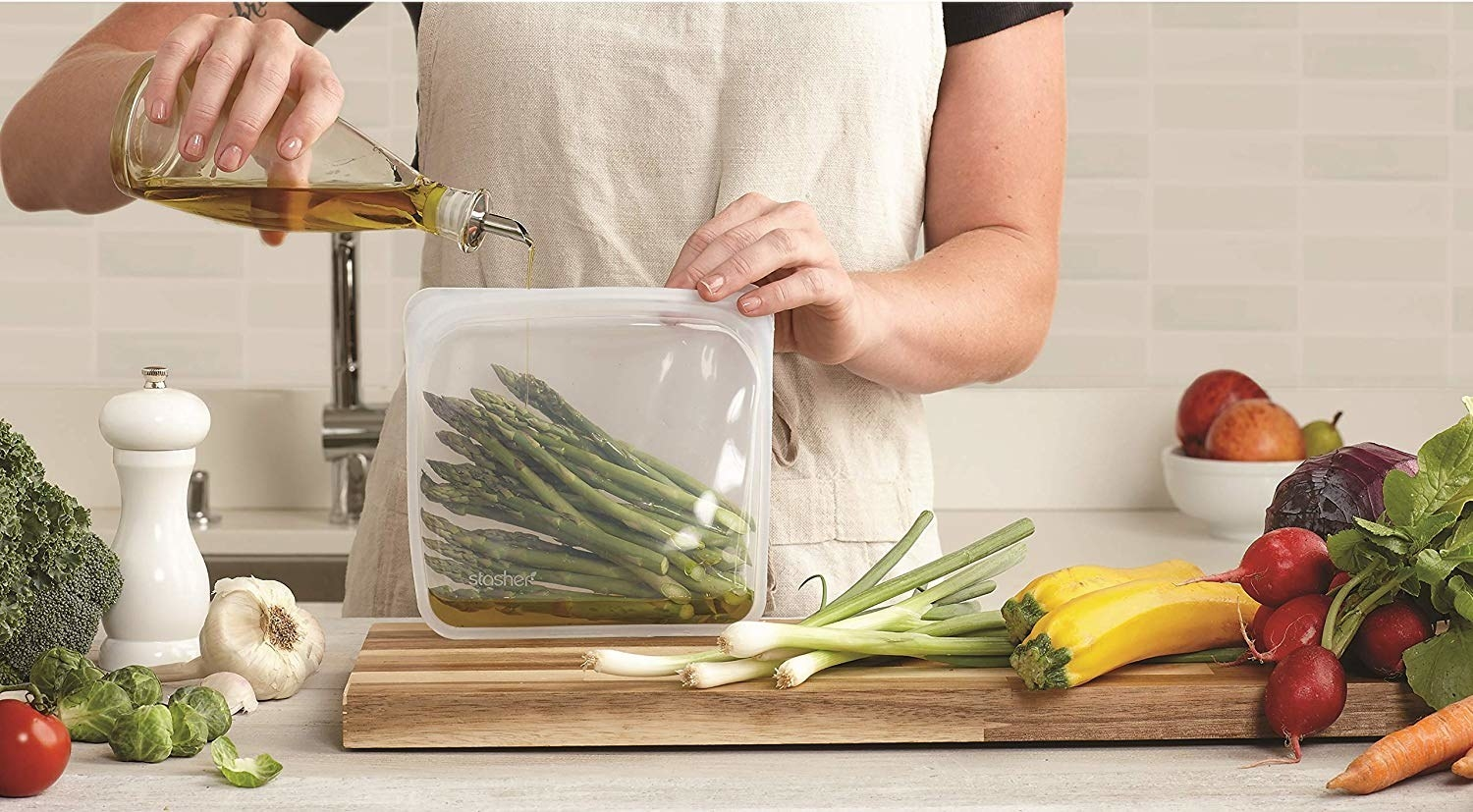 a person pouring olive oil into asparagus that are in the reusable bag