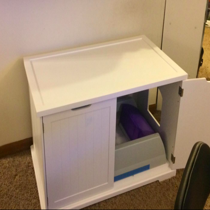 a reviewer's image of the litter box tucked away inside of the housing unit