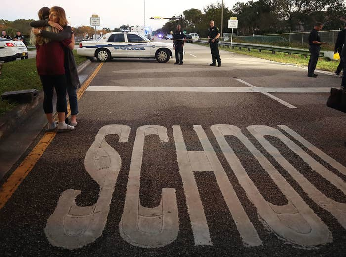 Mourners console each other near the Marjory Stoneman Douglas High School on Feb. 15, 2018, in Parkland, Florida.