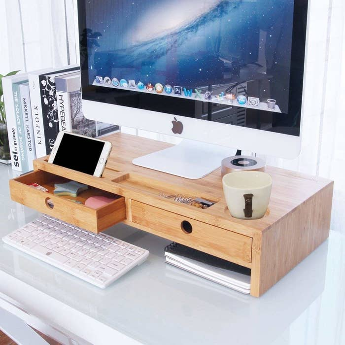 the stand rise with two storage drawers propping up a desktop and an iphone