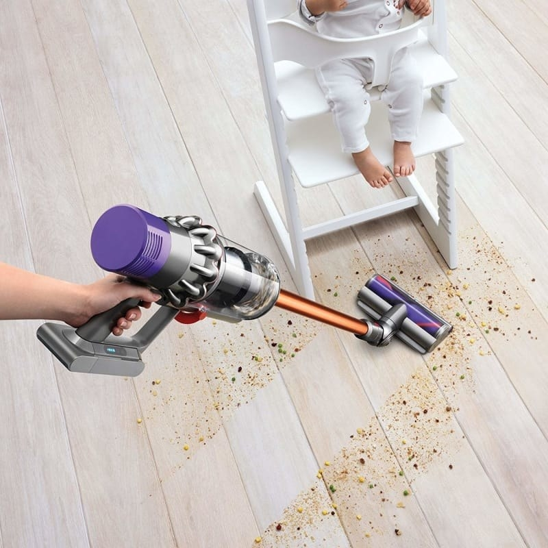 The cordless vacuum being used to clean up a mess of food under a high chair