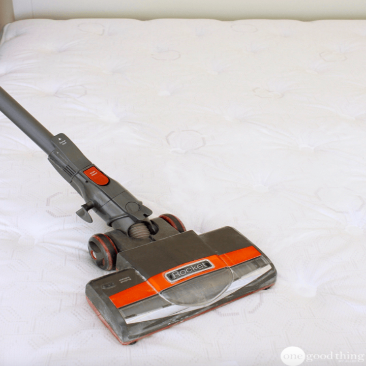 Person vacuuming the bed