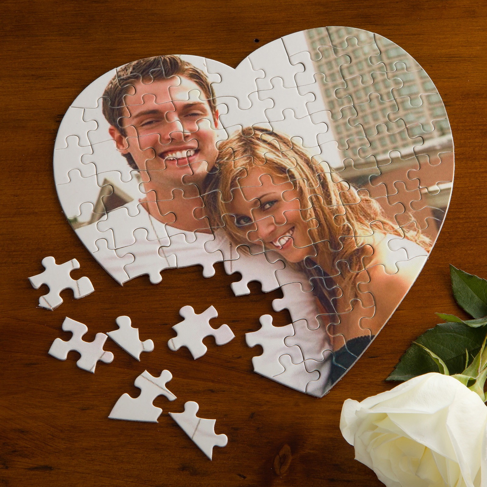 A photo of a smiling couple is printed on a half-completed heat-shaped puzzle on a wooden table next to a white rose .
