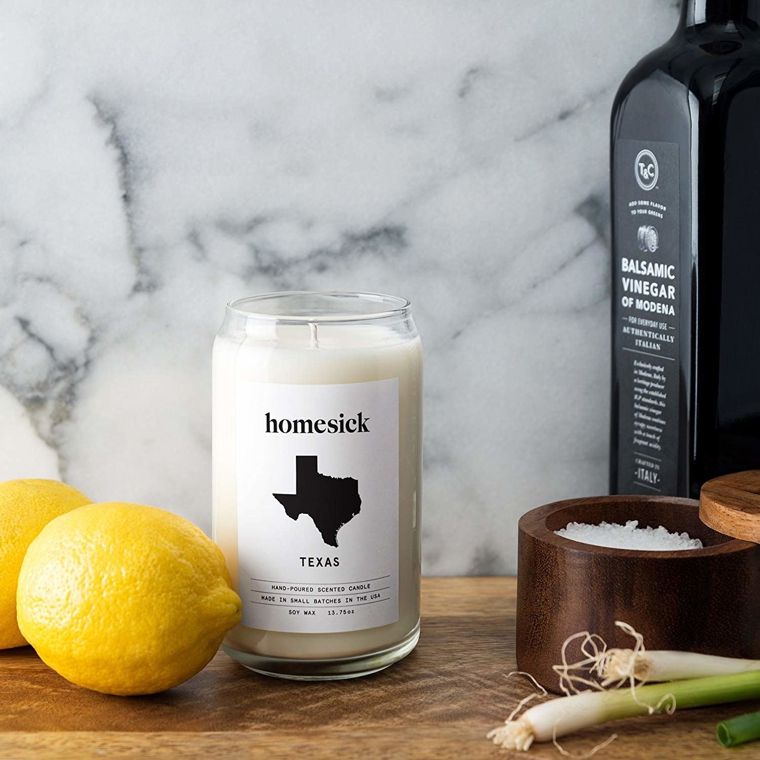 "A candle with a picture of Texas whose label reads ""Homesick: Texas"" sits on a kitchen table."