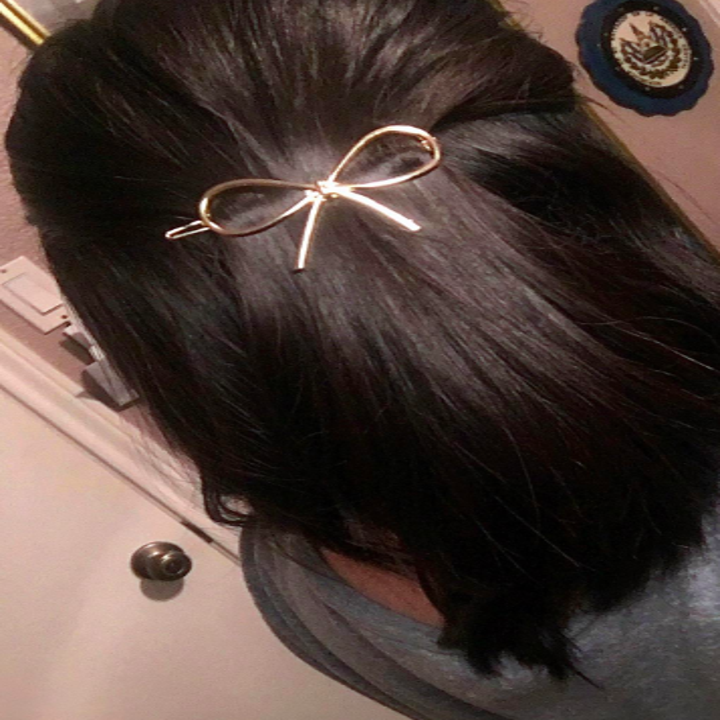 A reviewer wearing the gold bow clip