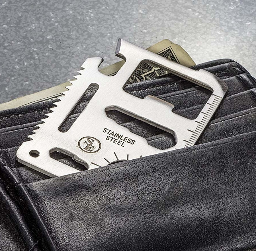 A silver multitool the size of a credit card is tucked into a black leather wallet, showcasing its ruler, bottle opener, and saw blade features.