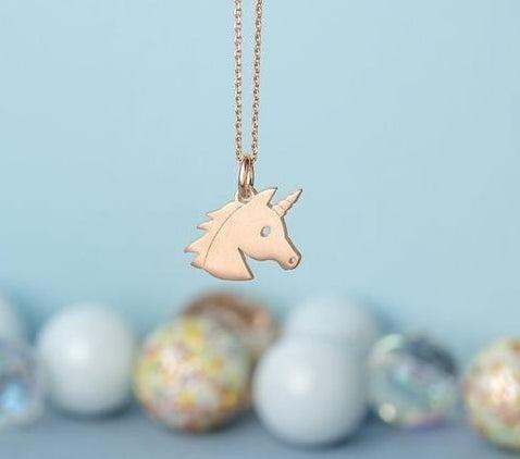 A rose gold unicorn head charm on a chain