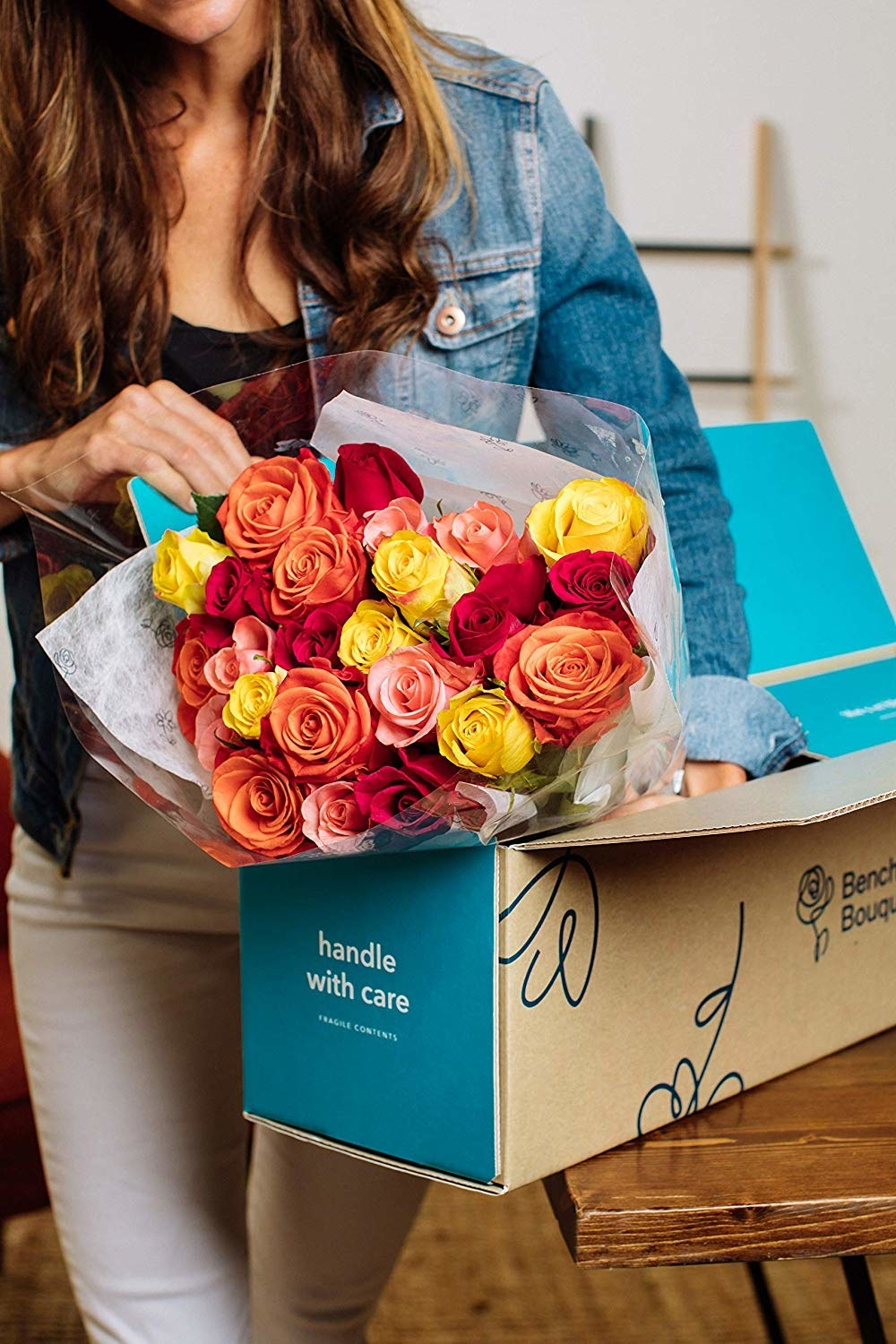 A person holding a box of Benchmark Bouquets