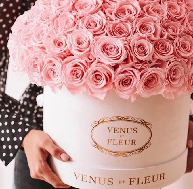 A person holding a large circle box of Venus ET Fleur flowers