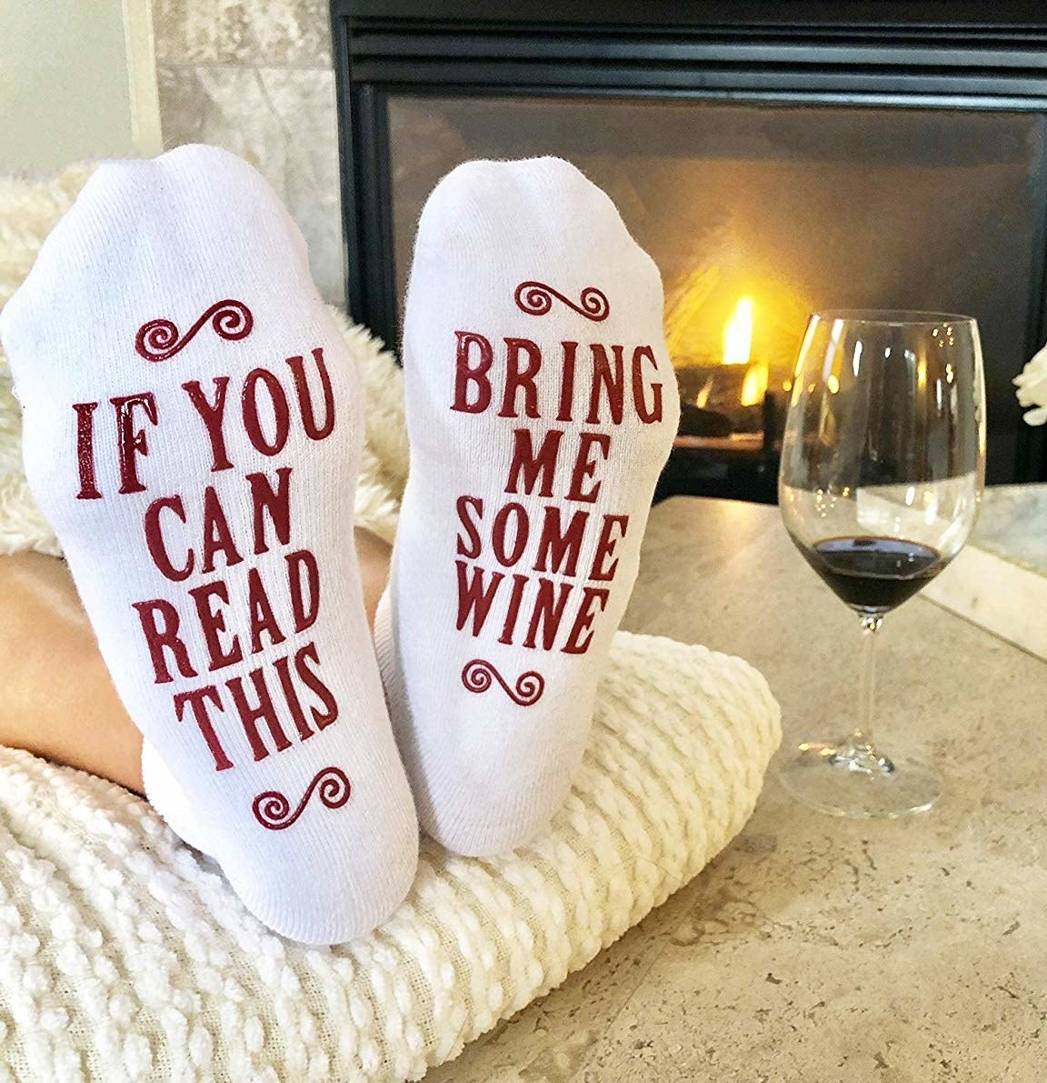 """Person with feet up wearing socks that say on the sole """"If you can read this bring me some wine"""""""