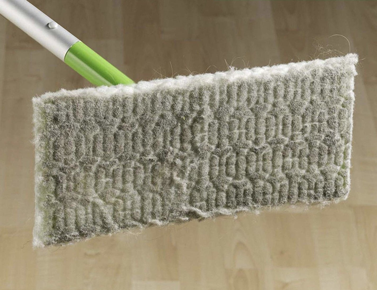 swiffer with a dry cloth full of dust
