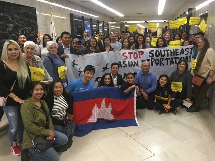 Advocates hold banners and signs backing pardons for Southeast Asian refugees who face deportation.