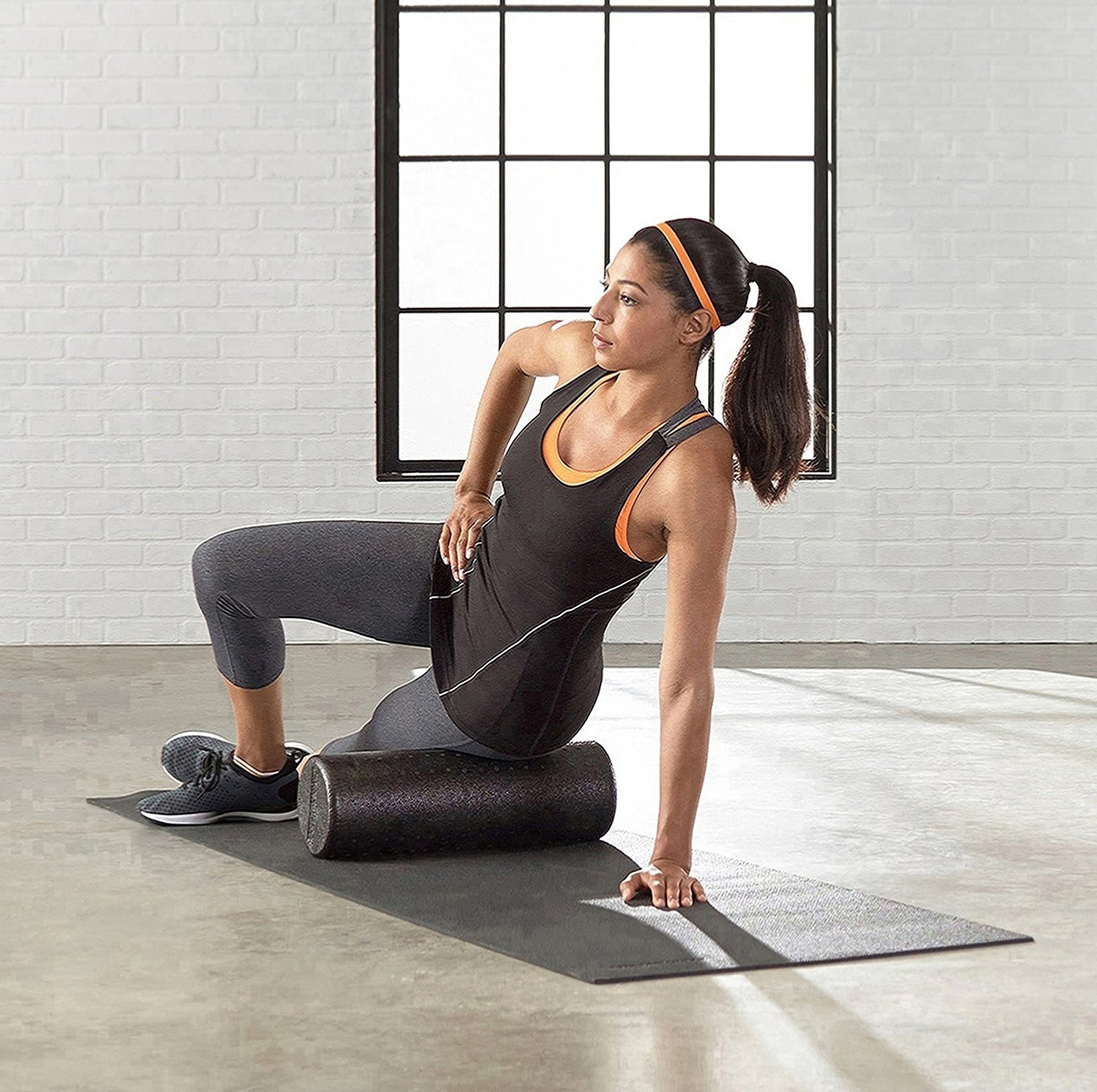 A model using a cylindrical foam roller on their thigh