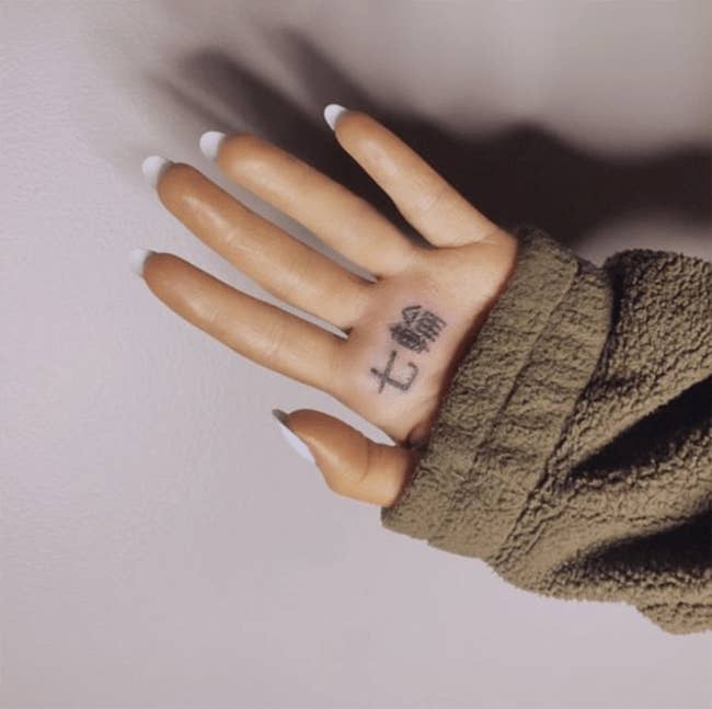 """But while the symbols used in the music video's title card — """"七つの指輪"""" — do translate to mean """"7 Rings"""", the tattoo cut out three of the characters, changing the meaning of the phrase completely.While the two symbols separately mean """"seven"""" (七) and """"ring"""" (輪), when you put them together they mean """"shichirin"""" — a small charcoal grill or BBQ."""