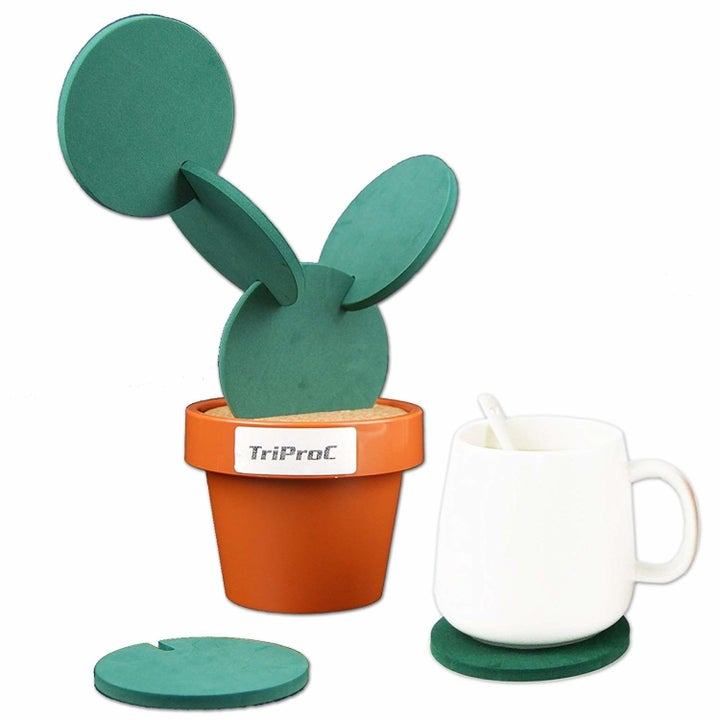 A brown flower pot with six circular coasters that, with slits on each side, slot onto each other to look like a cactus tower