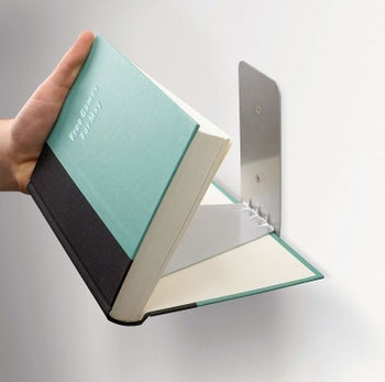 Book being attached to floating shelf
