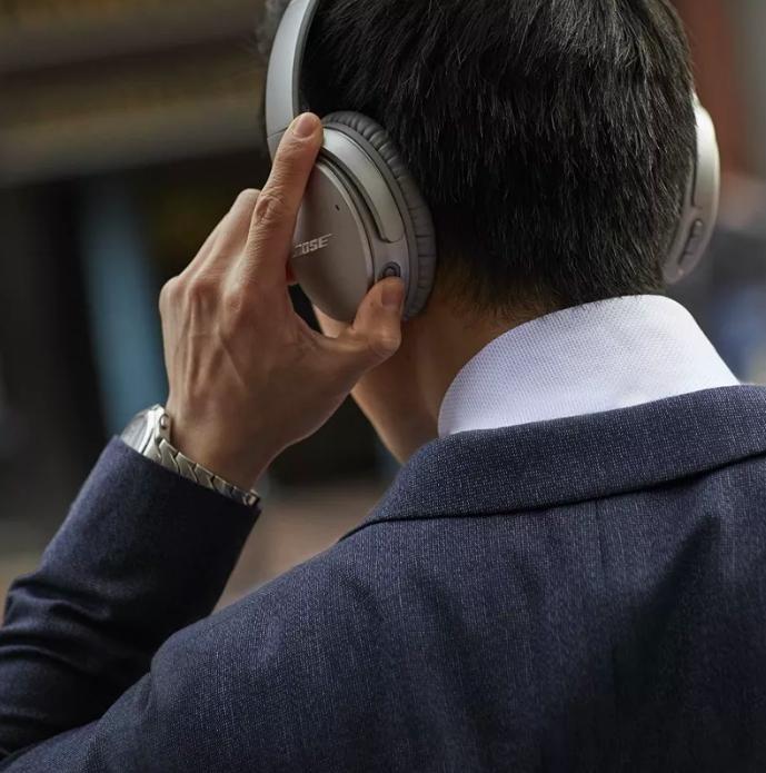 model wearing silver bose headphones