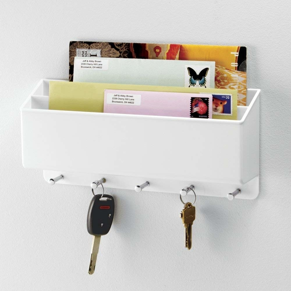Mail in wall organization system, keys dangling on hooks