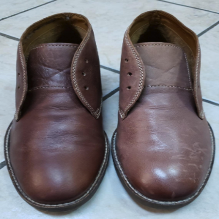 a reviewer's photo showing one shoe shiny and clean and the other looking worn out and stained