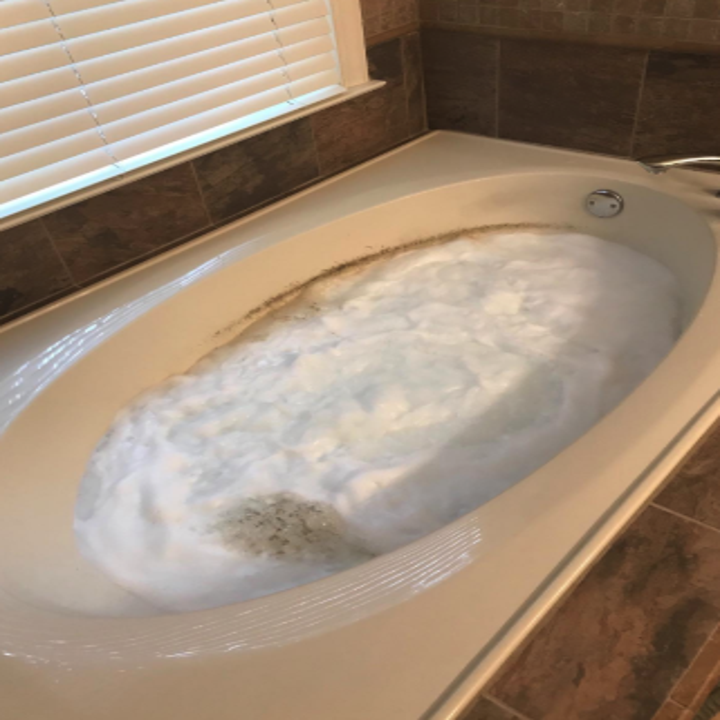 a reviewer's tub filled with suds and brown gunk