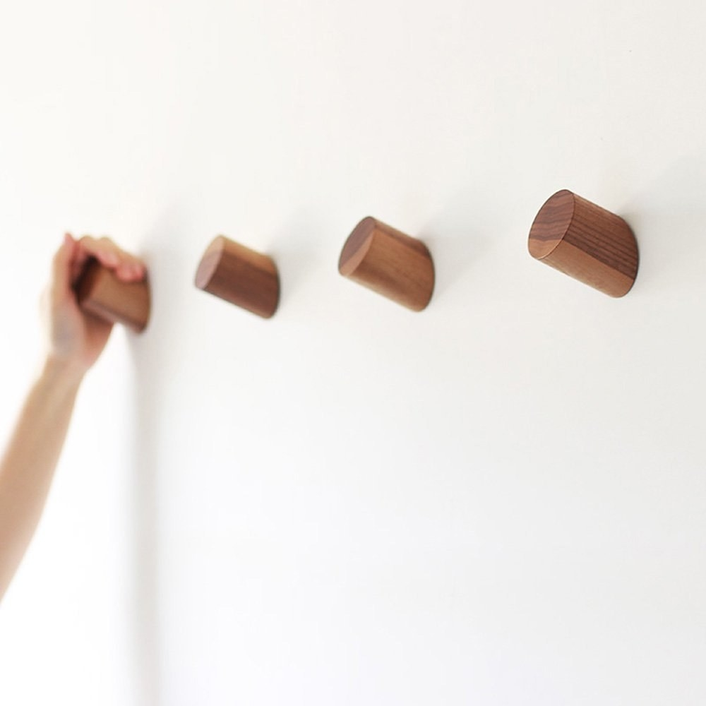 Four natural wood hooks on wall