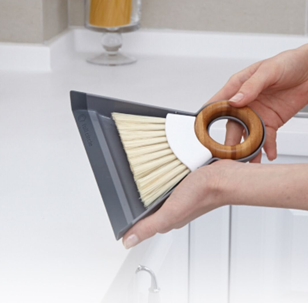 Mini bamboo brush and dustpan in hand