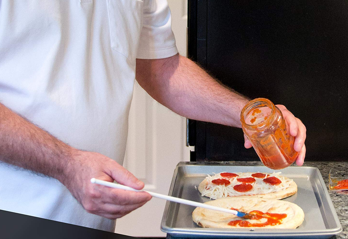 Spatty being used to apply tomato sauce to pizza crust