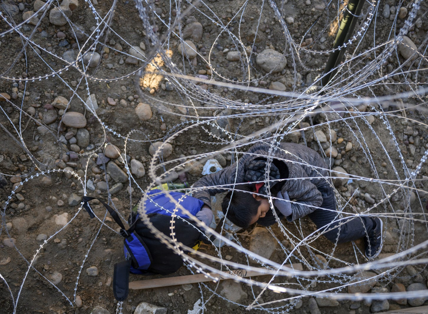 Kevin Andres, a Mexican migrant child from Oaxaca, crawls to retrieve his backpack from barbed wire after jumping the border fence to get into the US from Tijuana, Mexico, Dec. 28.