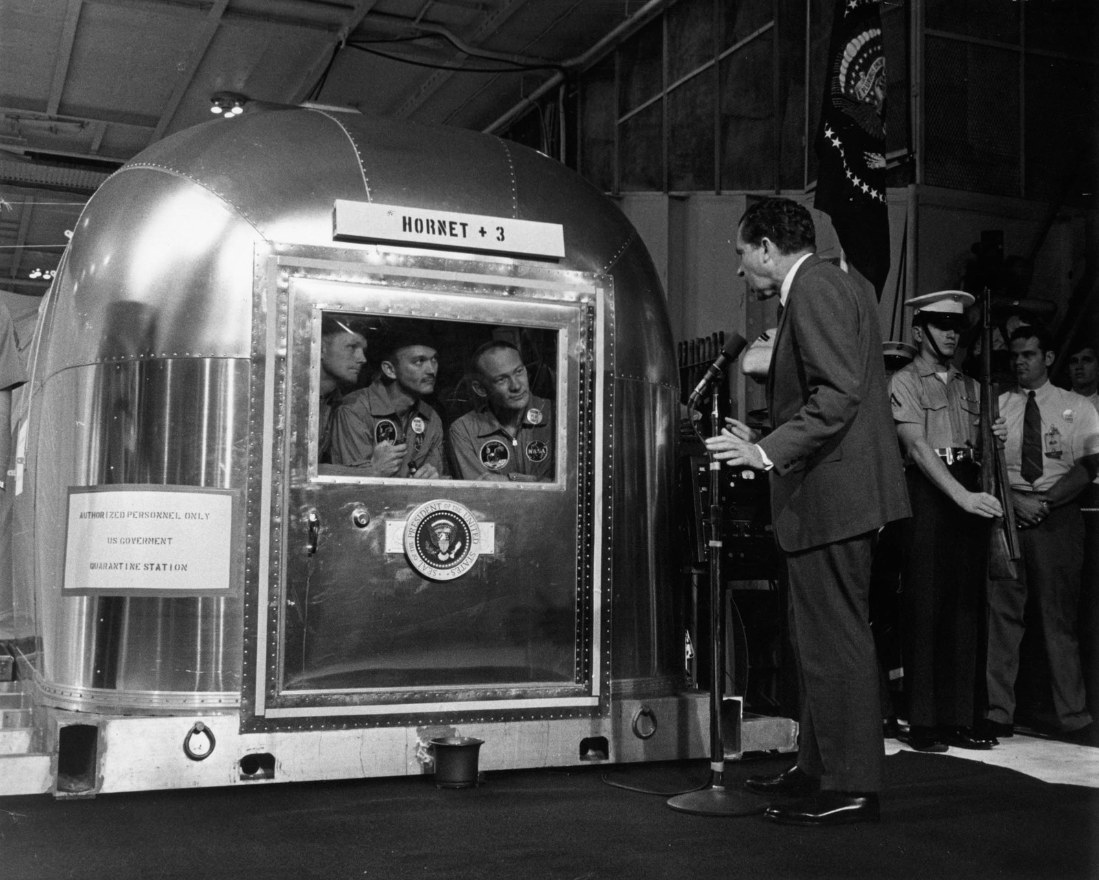 1969 President Richard M Nixon addresses astronauts (from left) Neil Armstrong, Michael Collins, and Buzz Aldrin, in their mobile quarantine facility aboard the USS Hornet. The astronauts were recovered from the Pacific Ocean on July 24 near Hawaii, after the first successful manned space flight to the moon. They will remain in quarantine for three weeks.
