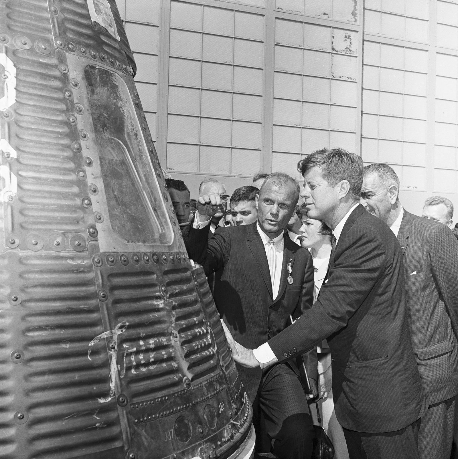 1962 John Glenn shows President Kennedy the Friendship 7, the space capsule that carried Glenn around the world three times in orbit. Glenn is wearing the medal presented to him by Kennedy. Vice President Lyndon Johnson is behind Kennedy.