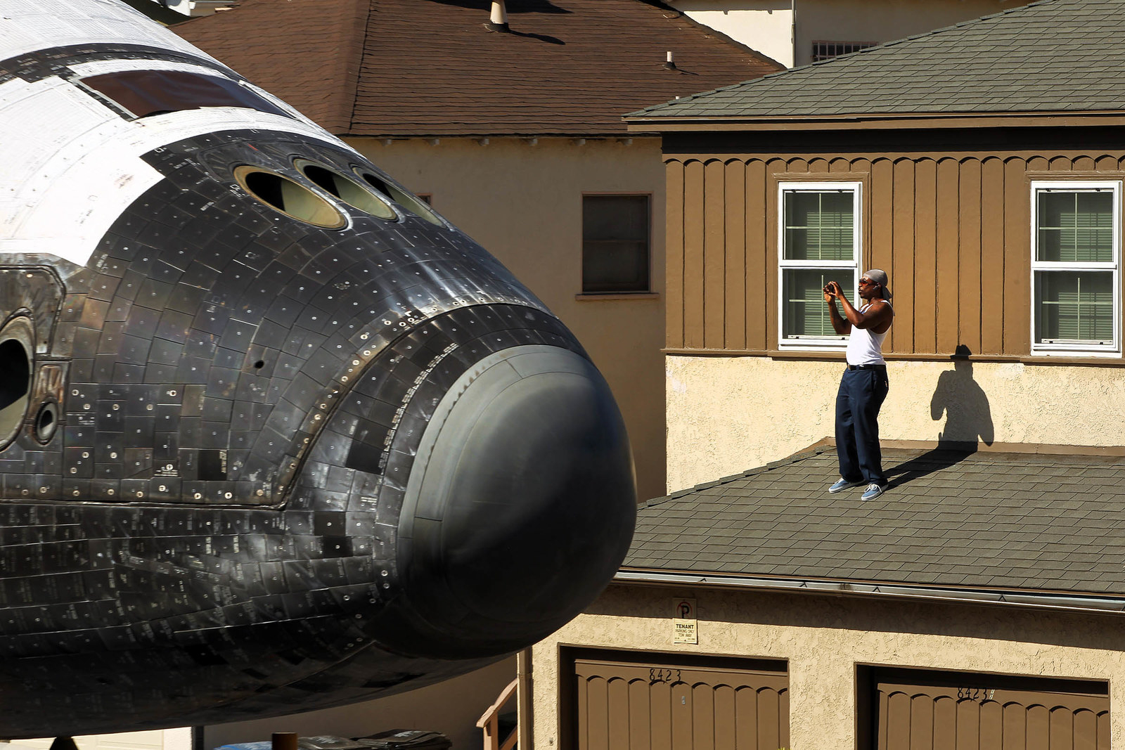 2012 A man takes a picture from a rooftop as the Endeavour Space Shuttle makes its way toward the California Science Center on Oct. 13, 2012, in Inglewood, California. Endeavour is on its last mission — a 12-mile creep through city streets, past an eclectic mix of strip malls, mom-and-pop shops, tidy lawns, and faded apartment buildings. Its final destination is the California Science Center in South Los Angeles where it will be put on display. NASA's Space Shuttle Program ended in 2011 after 30 years and 135 missions.