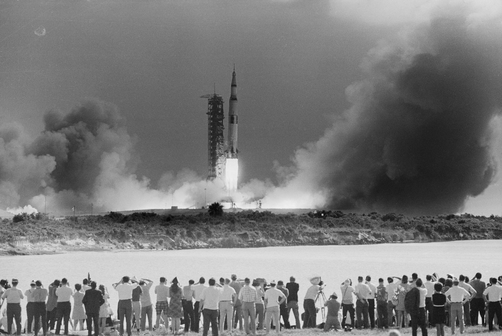 1969 The Apollo 11 mission gets underway at 9:32 a.m., as the Saturn V rocket, carrying the spacecraft on its nose, blasts off. This photo shows a small part of the vast throng that flocked to Cocoa Beach to witness the spectacle seconds after ignition. Apollo 11 landed the first men on the moon.