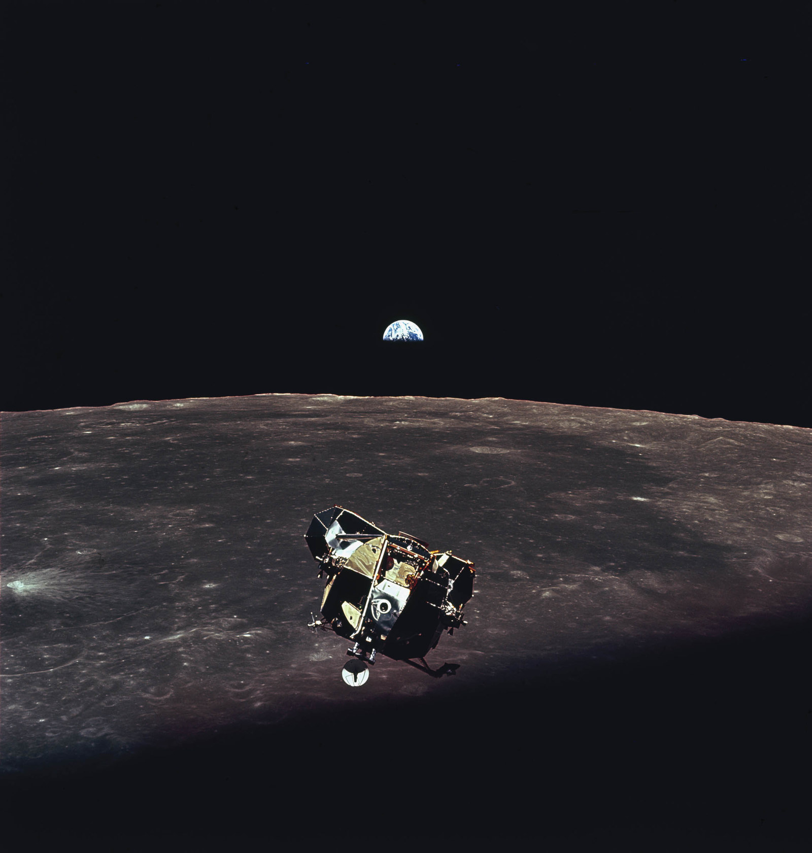1969 The Apollo 11 lunar module ascent stage photographed from the command service module during rendezvous in lunar orbit. Planet Earth is visible above the lunar horizon.
