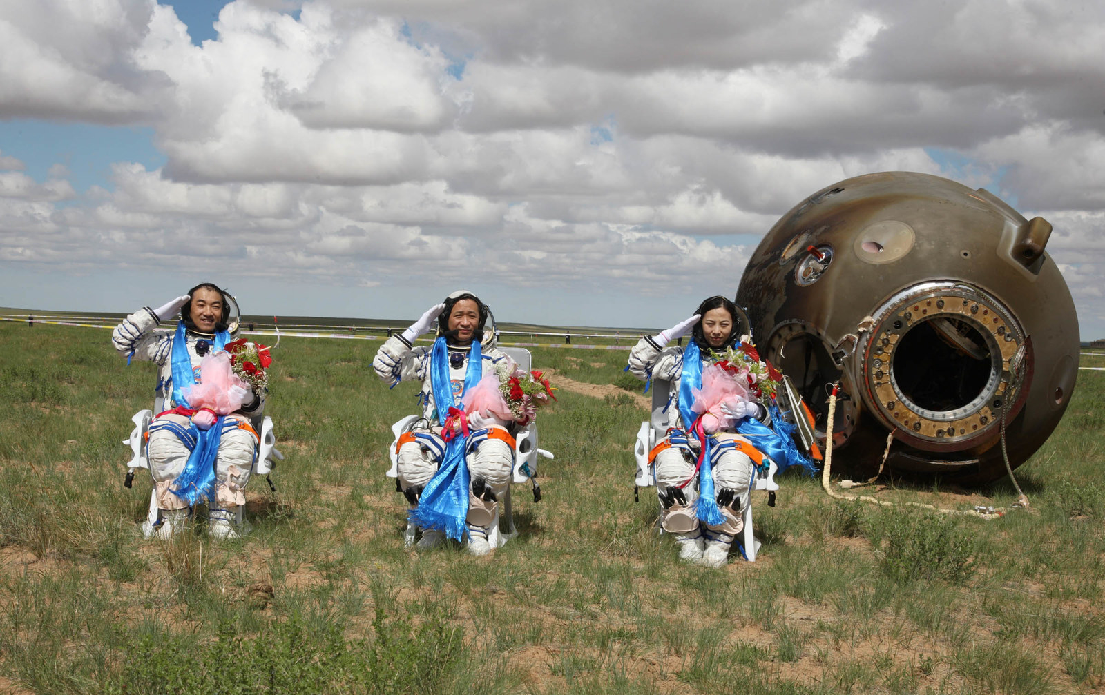 2013 Chinese astronauts Zhang Xiaoguang, Nie Haisheng, and Wang Yaping salute after getting out of the re-entry capsule of China's Shenzhou X spacecraft following its successful landing at the main landing site on June 26, 2013, in the Inner Mongolia Autonomous Region of China. The astronauts returned after a 15-day trip to a prototype space station.