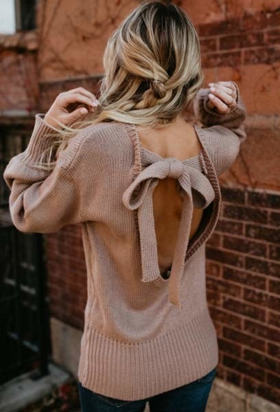A model in the brown sweater showing the open back with tie