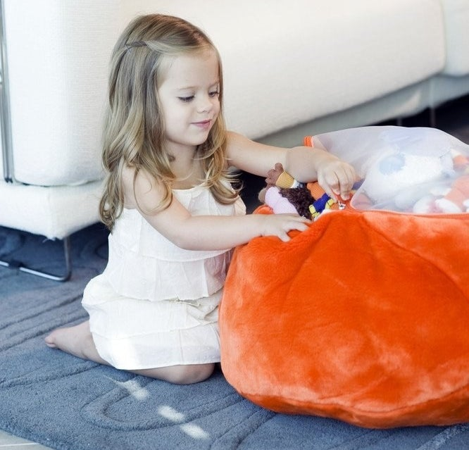 A small child stuffing the bean bag with their toys