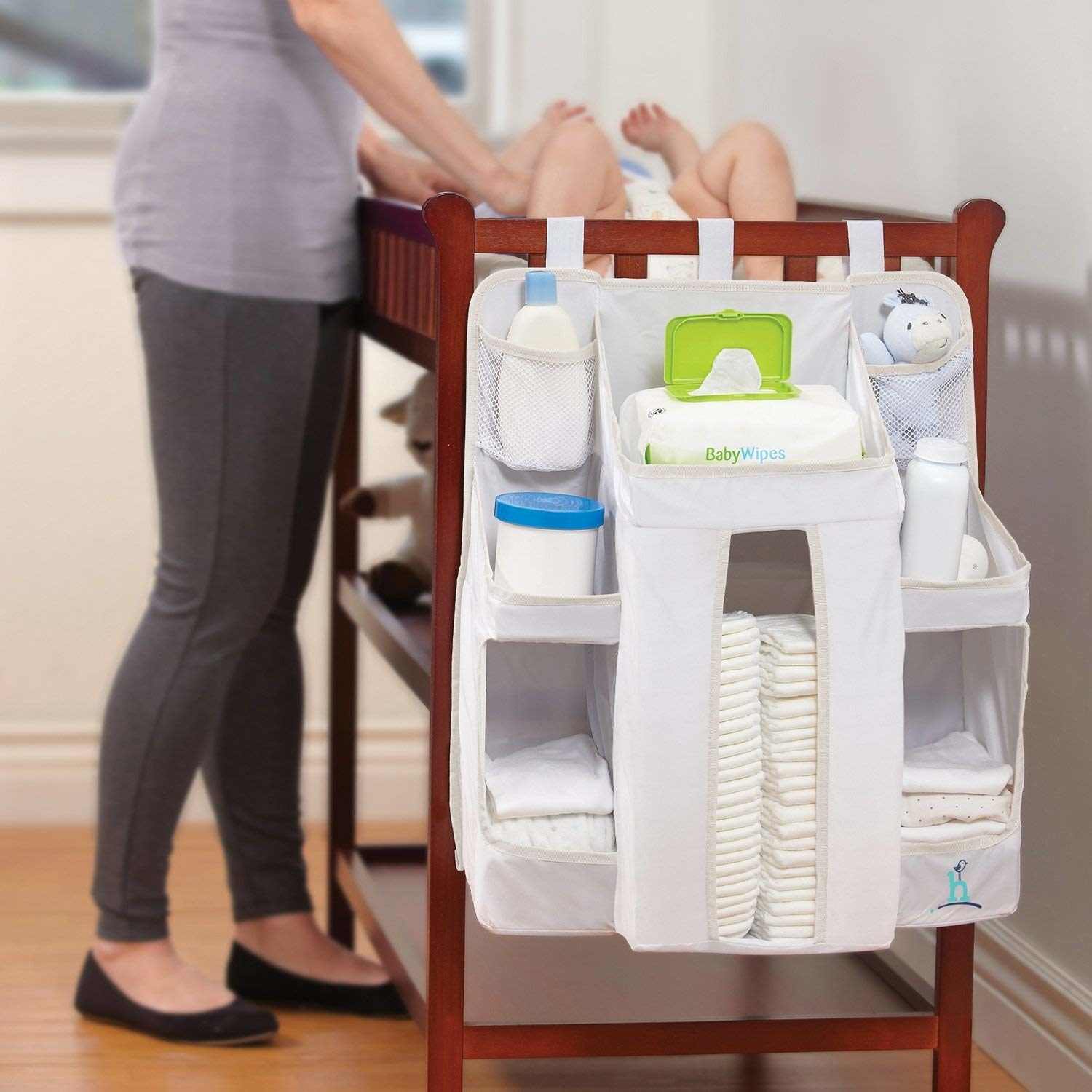 The diaper caddy attached to the side of a changing table