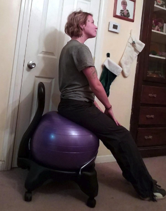 a reviewer sitting on a chair with the purple exercise ball as a seat