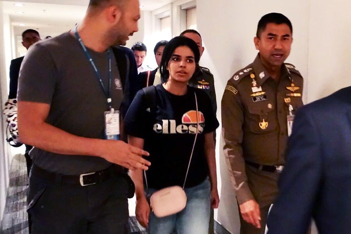 Rahaf Mohammed al-Qanun being escorted out of the Bangkok airport.