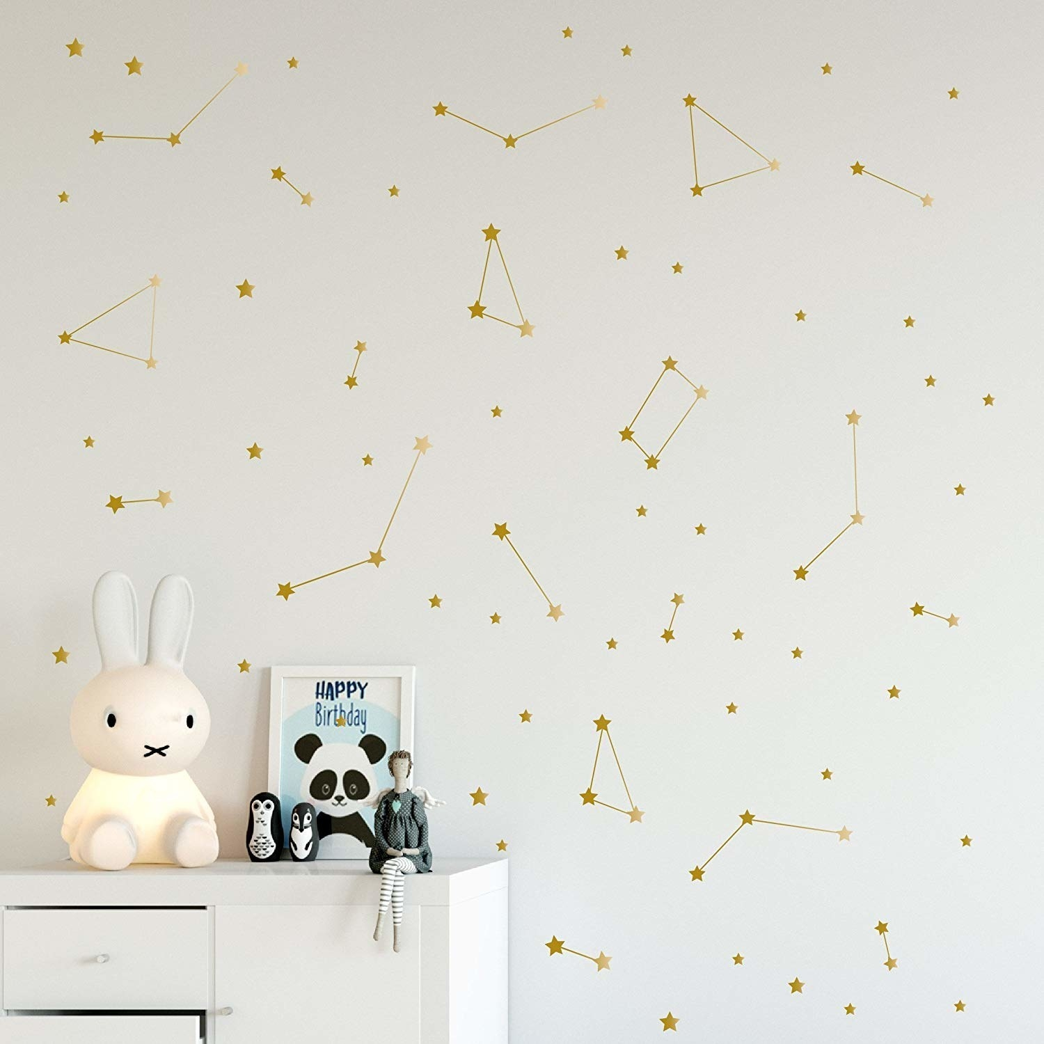 Little gold minimalist stickers with star and constellation shapes on a wall