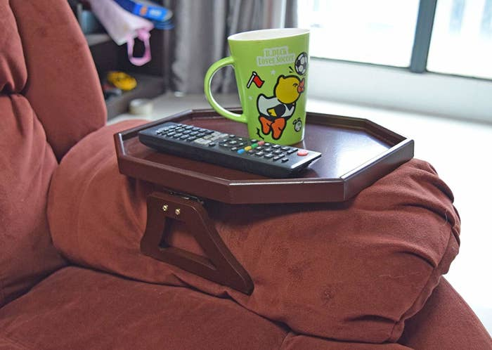 brown octagon-shaped small table with legs around the arm of a couch with a coffee mug and remote sitting on it
