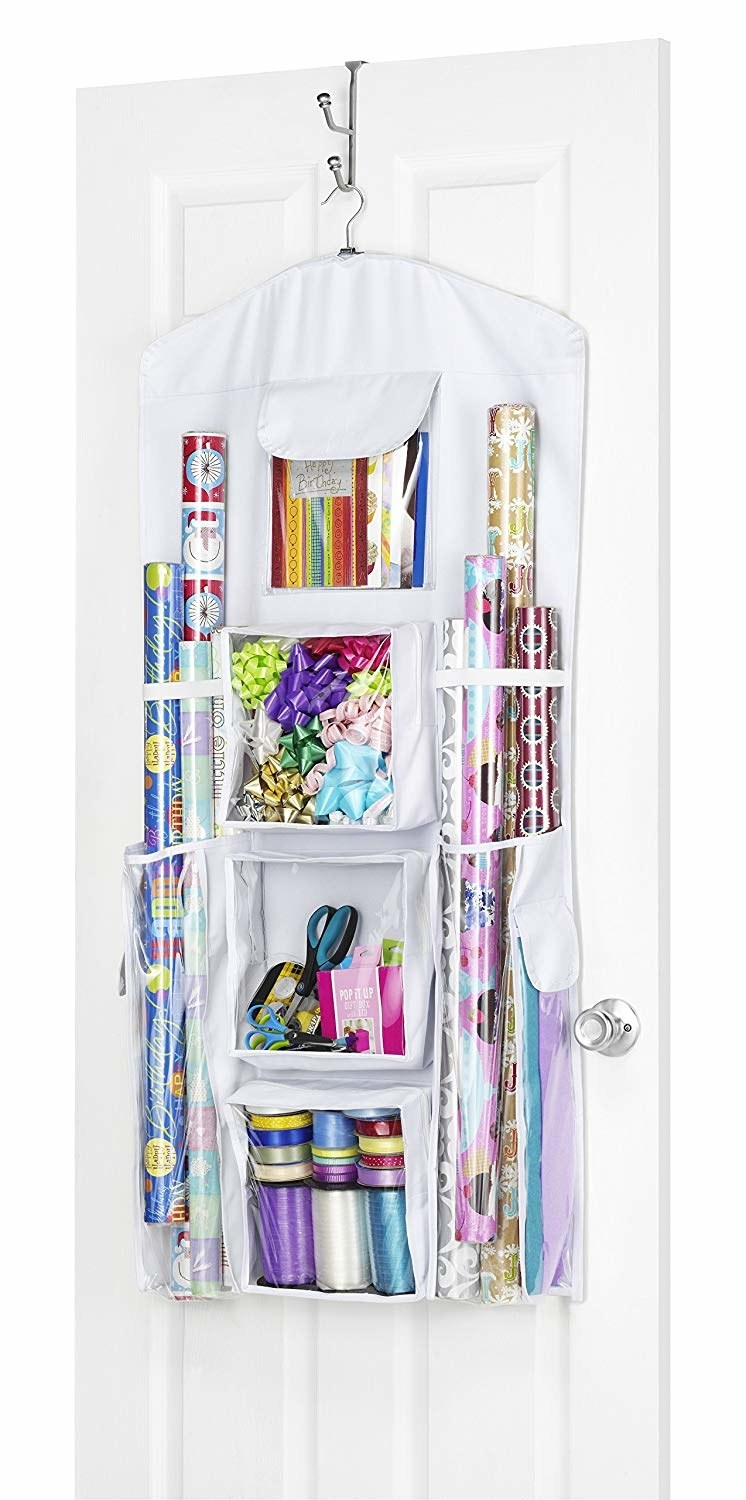 The over-the-door organizer hanging filled with wrapping paper, bows, and ribbon