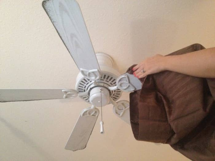 Blogger reaches up and grabs the pillowcase in two hands around a fan blade