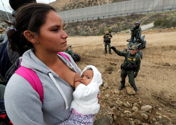 A woman holds her baby next to the border wall as she tries to cross illegally, in Tijuana, Mexico, on Dec. 14.