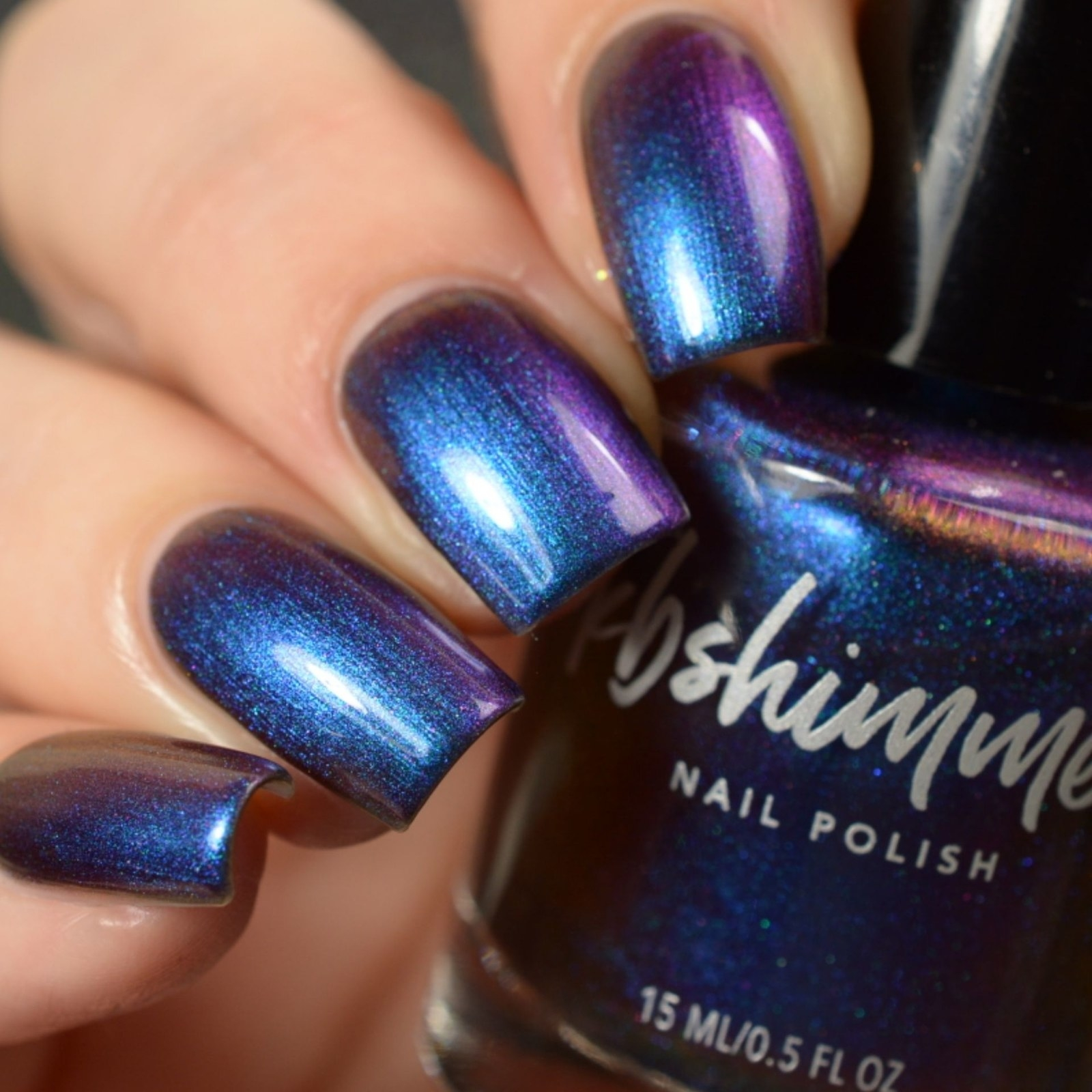 model holding the nail polish bottle with shiny iridescent blue nails