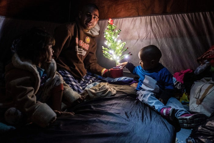 Members of a Honduran family pose for a picture with a Christmas tree inside their tent at a temporary shelter in downtown Tijuana, Mexico, on Dec. 18.