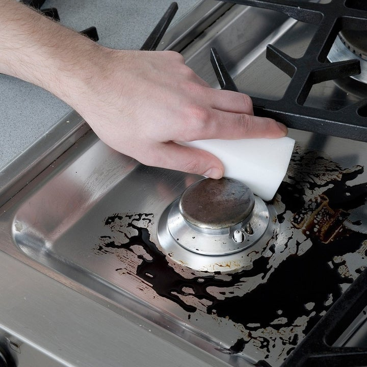 hand using foam sponge to scrub away cooked-on stain from stove